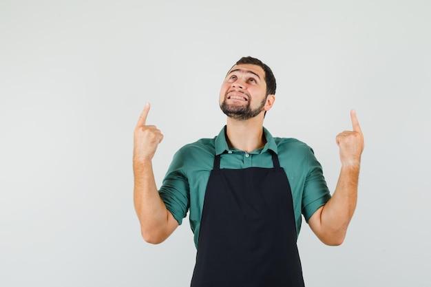 Jeune jardinier pointant vers le haut en t-shirt, tablier et semblant joyeux, vue de face.
