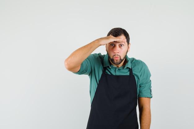 Jeune jardinier regardant sous sa paume en t-shirt, tablier, vue de face.
