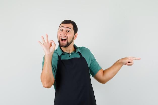 Jeune jardinier en t-shirt, tablier montrant un geste correct tout en pointant de côté et en ayant l'air joyeux, vue de face.