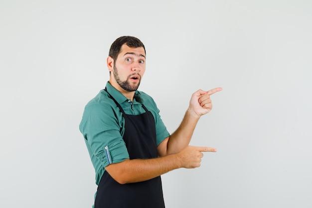 Jeune jardinier en t-shirt, tablier pointant de côté et l'air surpris, vue de face.