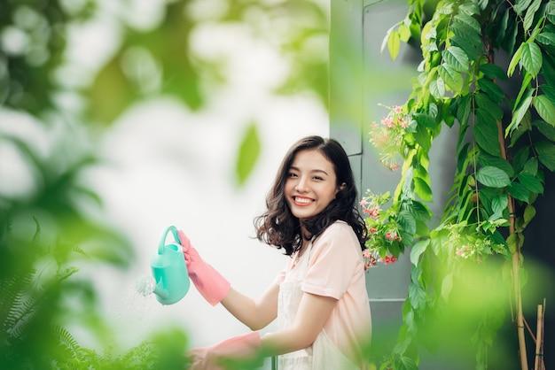 Jeune jardinière asiatique arrosant les plantes