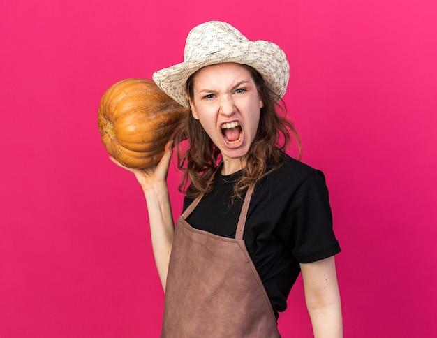 Jeune jardinière en colère portant un chapeau de jardinage tenant une citrouille isolée sur un mur rose
