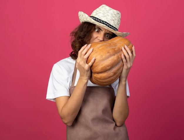 Jeune jardinière en colère en uniforme portant chapeau de jardinage tenant et regardant la citrouille