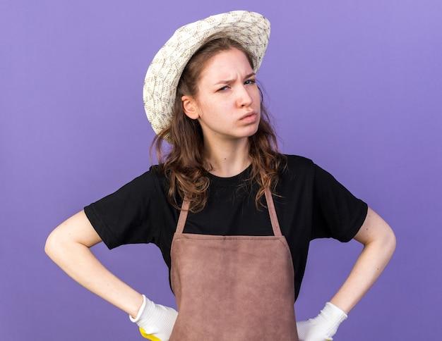 Jeune jardinière confiante portant un chapeau de jardinage avec des gants mettant les mains sur la hanche isolée sur le mur bleu