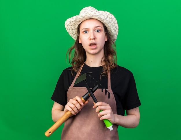Jeune jardinière confuse portant un chapeau de jardinage tenant et traversant un râteau avec un râteau à houe