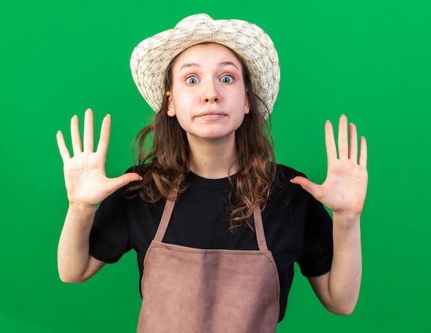 Jeune jardinière impressionnée portant un chapeau de jardinage levant les mains isolées sur un mur vert