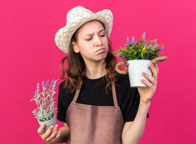 Jeune jardinière mécontente portant un chapeau de jardinage tenant et regardant des fleurs dans des pots de fleurs isolés sur un mur rose