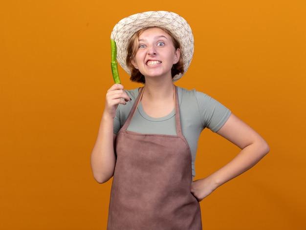 Jeune jardinière slave agacée portant un chapeau de jardinage tenant du piment cassé