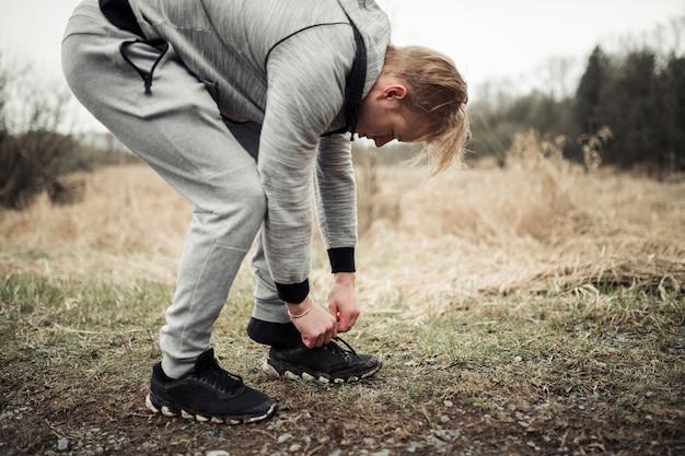 Jeune jogger mâle mettant ses chaussures de sport