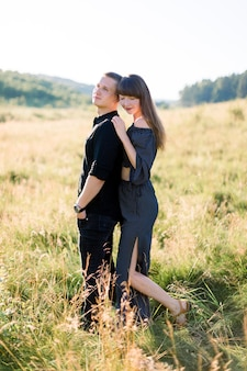 Jeune joli couple amoureux, vêtu de vêtements noirs élégants, posant en plein air dans la prairie d'été