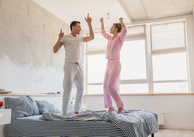 Jeune joli couple s'amusant sur le lit le matin rester ensemble à la maison seul