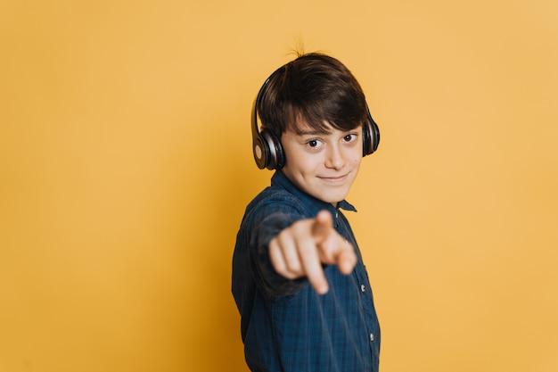 Jeune joli garçon dans les écouteurs, vêtu d'une chemise décontractée, mignon sourire, pointant vers vous sur fond jaune. faites votre choix.