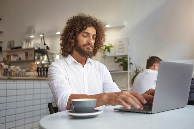 Jeune joli homme d'affaires en chemise blanche avec barbe et cheveux bouclés bruns assis à table au café, travaillant à distance avec son ordinateur portable, ayant une tasse de thé