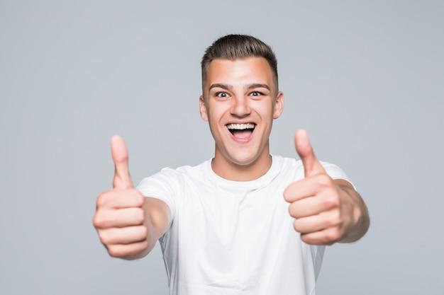 Jeune joli homme dans un t-shirt blanc isolé sur blanc tenir les pouces vers le haut