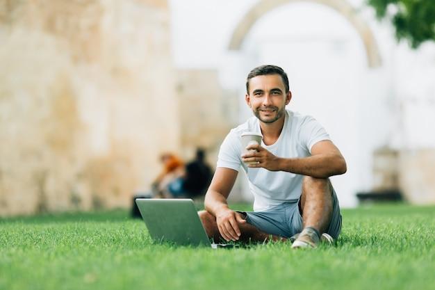 Jeune joli petit ami étudiant assis sur une herbe dans un campus