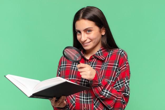 Jeune jolie adolescente. expression heureuse et surprise. recherche dans un concept de livre