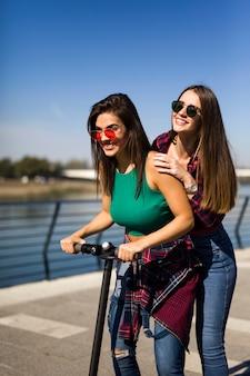 Jeune et jolie amies conduisant un scooter électrique dans la rue