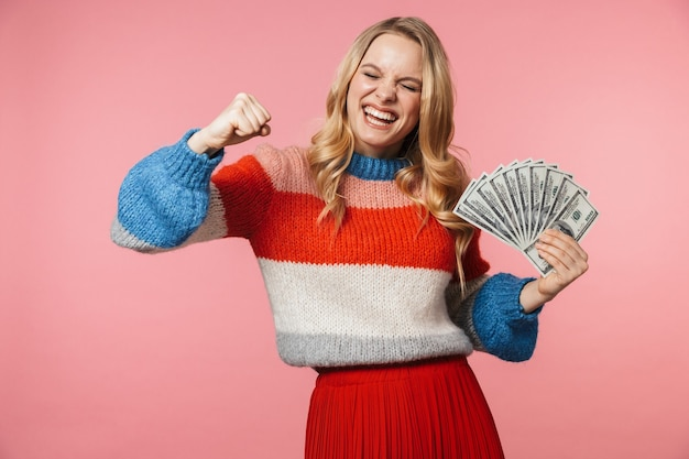Jeune jolie belle femme posant isolée sur un mur rose tenant de l'argent