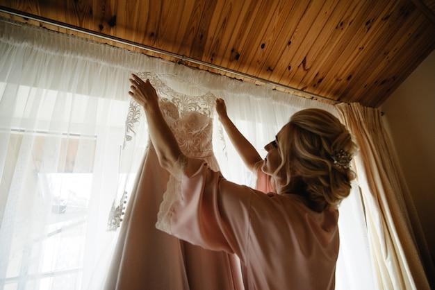 Jeune jolie blonde mariée regardant sa robe de mariée