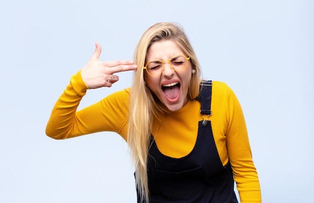 Jeune jolie blonde à la recherche de malheureux et stressé, geste de suicide faisant signe de pistolet avec la main, pointant la tête contre le mur plat