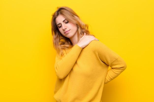Jeune jolie blonde se sentant fatiguée, stressée, anxieuse, frustrée et déprimée, souffrant de douleurs au dos ou au cou contre le mur jaune