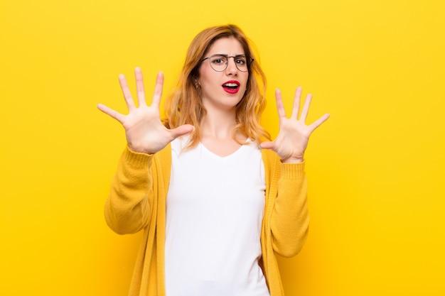 Jeune jolie blonde se sentant stupéfaite et effrayée, craignant quelque chose d'effrayant, avec les mains ouvertes devant lui disant de rester à l'écart du mur jaune