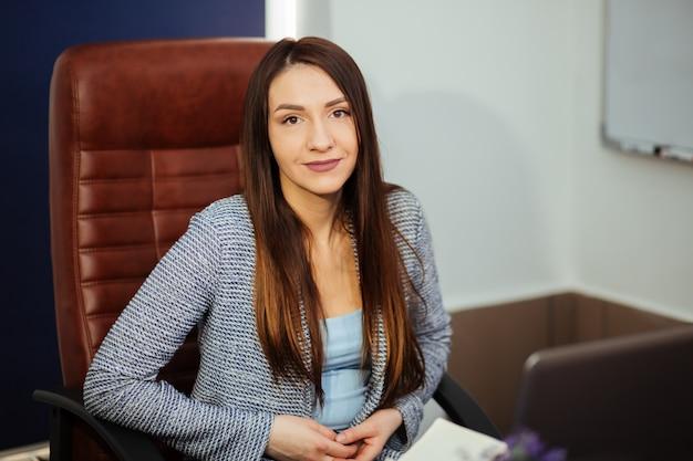 Jeune jolie brune caucasienne, heureuse belle femme d'affaires en costume de cardigan d'affaires est assis à table dans le bureau lumineux. portrait d'homme d'affaires, directeur de l'organisation. femme au travail