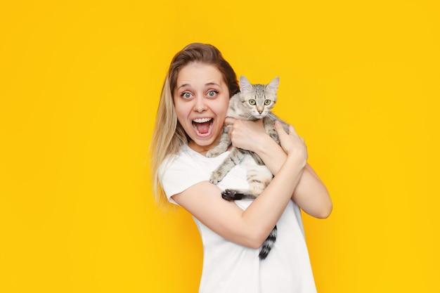 Une jeune jolie caucasienne impressionnée par une femme blonde souriante dans un t-shirt blanc avec un chat dans les mains est heureuse de la nouvelle isolée sur un mur jaune de couleur vive