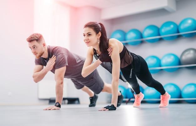Jeune et jolie couple faisant des exercices ensemble dans la salle de sport légère.