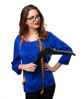 Jeune et jolie couturière avec un ruban à mesurer et un cintre