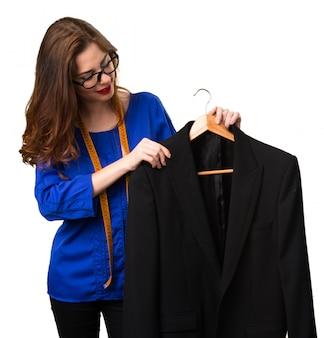 Jeune et jolie couturière avec un ruban à mesurer et un costume