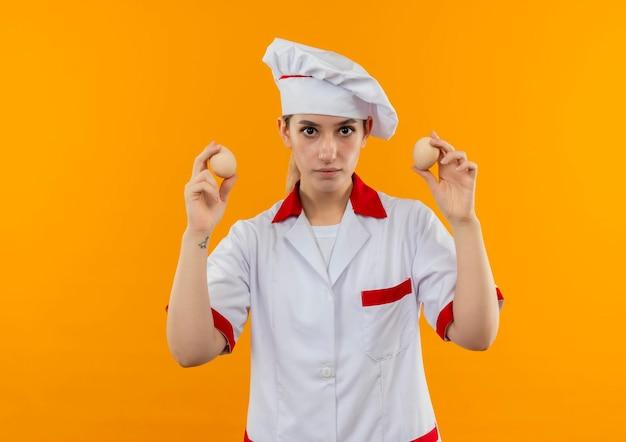 Jeune jolie cuisinière impressionnée en uniforme de chef tenant des œufs isolés sur un mur orange