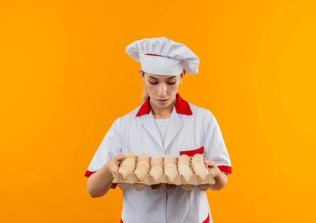 Jeune jolie cuisinière impressionnée en uniforme de chef tenant et regardant un carton d'œufs isolé sur un mur orange