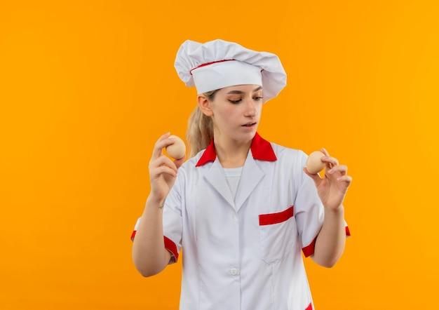 Jeune jolie cuisinière impressionnée en uniforme de chef tenant et regardant des œufs isolés sur un mur orange