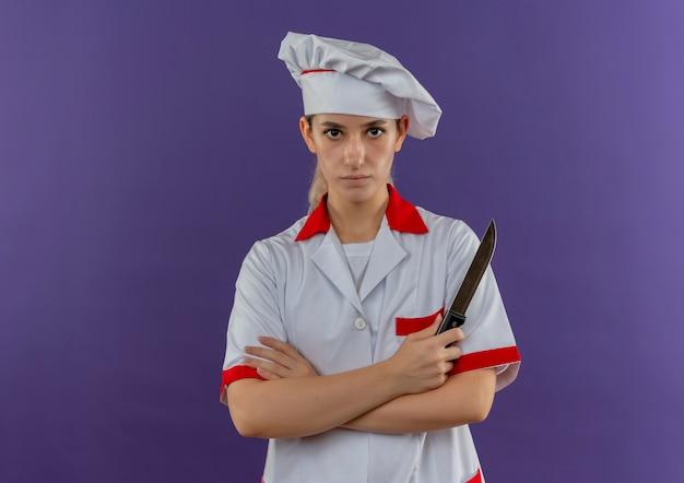 Jeune jolie cuisinière en uniforme de chef debout avec une posture fermée tenant un couteau et à la recherche