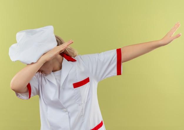 Jeune jolie cuisinière en uniforme de chef faisant le geste de dab isolé sur fond vert