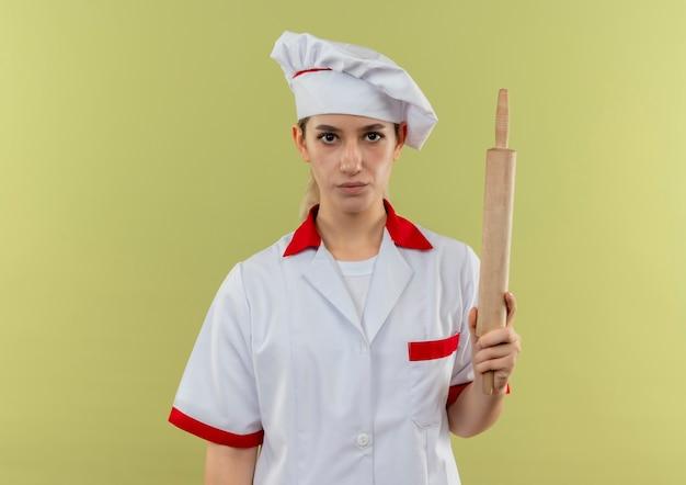 Jeune jolie cuisinière en uniforme de chef tenant le rouleau à pâtisserie isolé sur fond vert