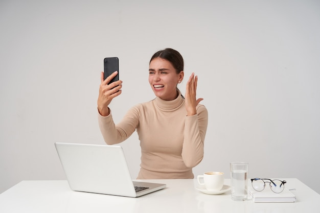 Jeune jolie dame aux cheveux noirs levant la main avec un smartphone tout en ayant une conversation téléphonique passionnante, travaillant au bureau avec un ordinateur portable moderne