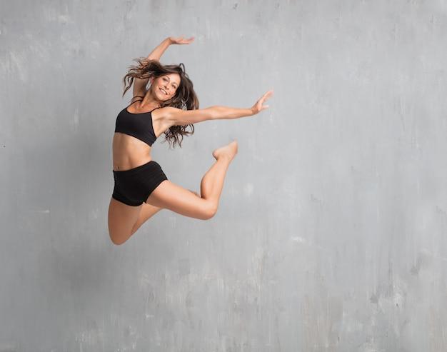 Jeune jolie danseuse de rue sautant contre un mur de grunge