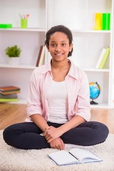 Jeune jolie écolière mulâtre assise sur le tapis.