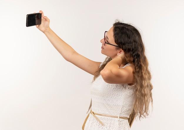 Jeune jolie écolière portant des lunettes et sac à dos debout en vue de profil en prenant selfie mettant la main sur le cou isolé sur fond blanc