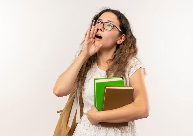 Jeune jolie écolière portant des lunettes et sac à dos tenant des livres en levant la main près de la bouche appelant à quelqu'un isolé sur fond blanc avec espace copie