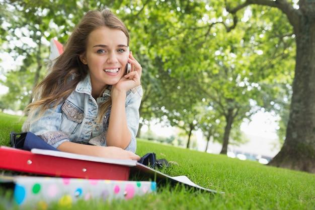 Jeune jolie étudiante allongée sur l'herbe au téléphone