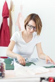 Jeune jolie étudiante étudie chez un créateur de vêtements à l'université et fait sa première thèse assise à un bureau avec une machine à coudre. concept de conception de vêtements.