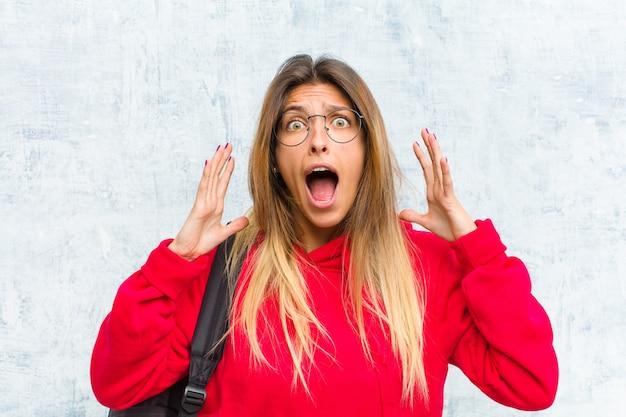 Jeune jolie étudiante hurlant avec les mains en l'air, furieuse, frustrée, stressée et contrariée