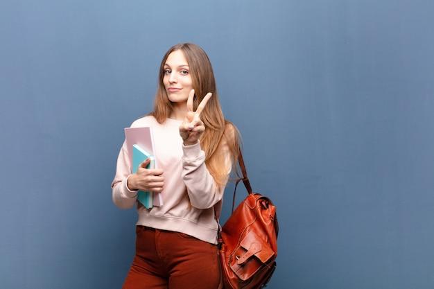 Jeune jolie étudiante avec des livres et un sac contre un fond bleu