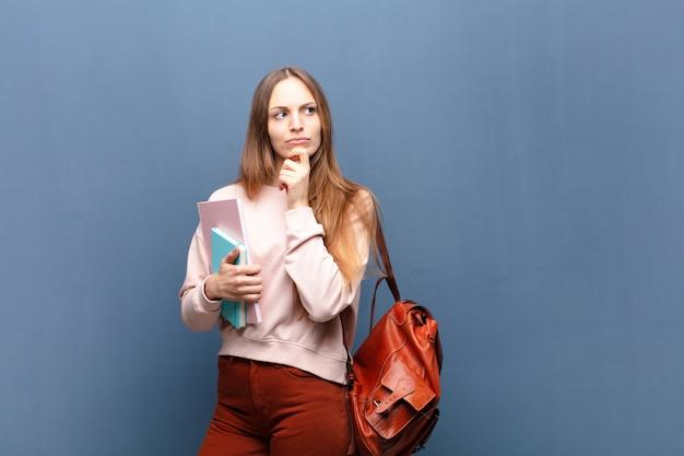 Jeune jolie étudiante avec livres et sac contre un mur bleu avec un espace de copie