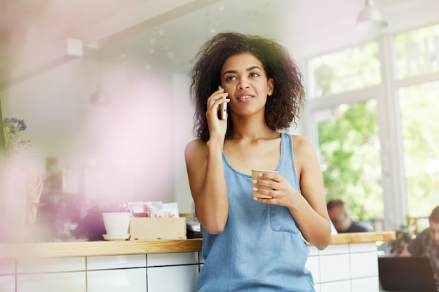 Jeune jolie étudiante à la peau sombre avec des cheveux ondulés sombres en chemise bleue décontractée parlant au téléphone avec son petit ami, regardant de côté avec une expression calme, buvant un café relaxant après l'étude