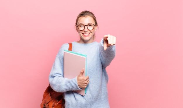Jeune jolie étudiante pointant vers la caméra avec un sourire satisfait, confiant et amical, vous choisissant