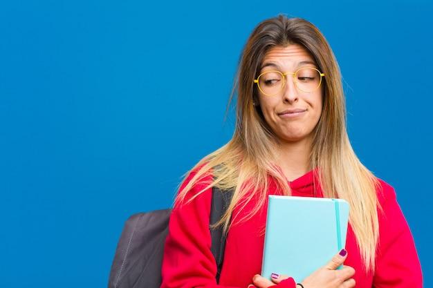 Jeune jolie étudiante se demandant, pensant avoir des pensées et des idées heureuses, rêvassant, cherchant à copier de l'espace